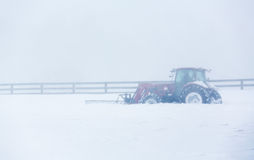 Modern tractor with plow clearing road in blizzard Stock Photography