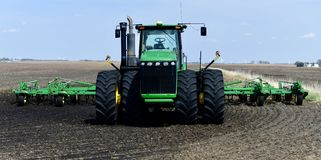 A Modern Tractor. This is a Spring picture of a modern tractor sitting in a freshly plowed field located in Hardin County. This massive tractor has air royalty free stock images