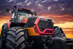 Modern tractor on sunset background. Tractor working on the farm, a modern agricultural transport, a farmer working in the field, tractor at sunset, modern royalty free stock image