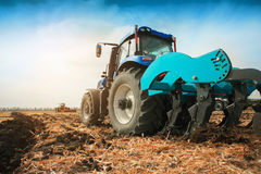 A modern tractor with a trailed plow on the field on a sunny day. Royalty Free Stock Photo