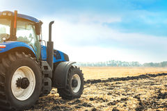 Modern tractor working in a field. Royalty Free Stock Images