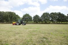 Tractor drives on pasture royalty free stock photo