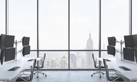 A modern trader's workplaces in a bright modern open space office. White tables equipped with modern trader's stations and black c. Hairs. New York panoramic Stock Photography