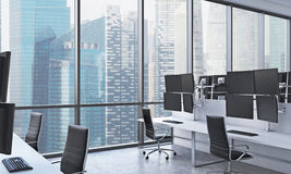 A modern trader's workplaces in a bright modern open space office. White tables equipped with modern trader's stations and black c Stock Photos