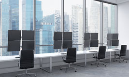 A modern trader's workplaces in a bright modern open space office. White tables equipped with modern trader's stations and black c Stock Images