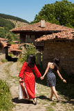 Modern and traditional. Costume women walking in the village streets of Jeravna Bulgaria Stock Photo