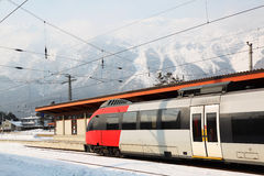 Modern train stops at station near mountains Royalty Free Stock Photo