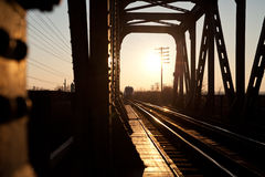 The train is coming!. An modern train is about to cross an old bridge into sunset light Stock Photo