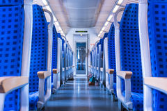 Modern Train Wagon Interior Seats Rows Blue Transportation White. Daytime Traveling Empty Royalty Free Stock Photo