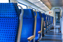 Modern Train Wagon Interior Seats Rows Blue Transportation White. Daytime Traveling Empty Royalty Free Stock Photos