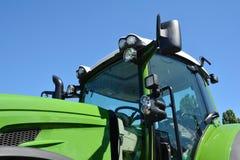 Modern traktorkabin Ny gr?n traktor med billyktor royaltyfria bilder