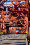 Modern tram on bridge with metal trusses in sunlight Royalty Free Stock Images