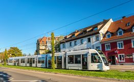 Modern tram in the city center of Freiburg im Breisgau, Germany. Freiburg im Breisgau, Germany - October 14, 2017: CAF Urbos 100 tram in the city center. The Royalty Free Stock Image