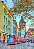Modern tram in the old town of Freiburg im Breisgau, Germany. Freiburg im Breisgau, Germany - October 14, 2017: Siemens Combino tram in the old town. The Royalty Free Stock Image