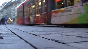 Modern tram passing crowded street in old city downtown, public transportation. Stock footage stock video