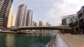 Modern tram passing over the bridge across the river among skyscrapers in Dubai Marina, UAE stock video footage