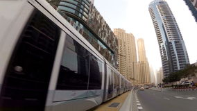 Modern tram rides on rails among the skyscrapers in Dubai, UAE. This tram goes around the Dubai Marina and connects the metro station with living quarter stock video