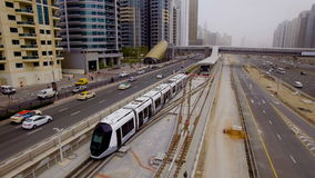 Modern tram travels on rails along the high-rise buildings in Dubai, UAE. Modern tram travels on rails along the high-rise buildings. It is white with tinted stock video