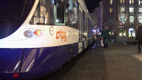 Modern tramcar leaving tram stop, active traffic in city downtown at night. Stock footage stock video footage
