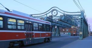 Modern transit vehicle on the Queen Street Bridge in Toronto at twilight 4K. A Modern transit vehicle on the Queen Street Bridge in Toronto at twilight 4K stock footage
