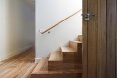 Modern trappuppgång av ekträ bredvid den horisontalytterdörren arkivbild