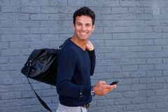 Modern travel man walking with mobile phone and bag Royalty Free Stock Image