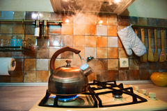 Modern, trendy, bronze kettle on a new modern kitchen. From the kettle going strong steam Stock Photos