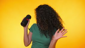 Modern trendy girl listening to music by wireless portable speaker. Young beautiful woman with curly hairstyle enjoying stock video