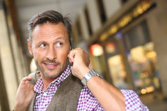 Modern trendy man talking on phone in street Royalty Free Stock Image