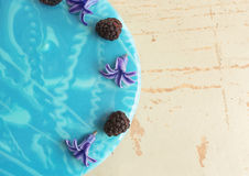 Modern trendy mousse cake with blue marble mirror glaze. Flowers and blackberries decor. Stock Photography