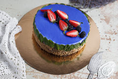 Modern trendy mousse cake with blue marble mirror glaze. strawberry and blackberries decor. Selective focus. Stock Photos