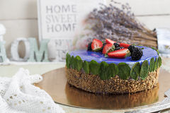 Modern trendy mousse cake with blue marble mirror glaze. strawberry and blackberries decor. Selective focus. Stock Image
