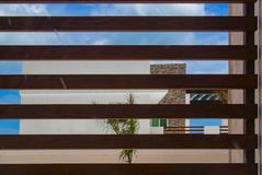 Modern tropical beach house against blue sky viewed through wooden slats royalty free stock photo