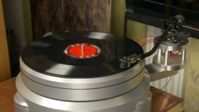 Modern turntable aluminium chassie with tonearm and vinil records rotation. Start playing.