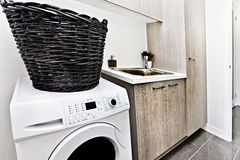 Modern tvättstuga med en tvagningmaskin och korg arkivfoton