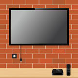 Modern TV with blank screen on brick wall and TV player box device with remote controller Stock Photos