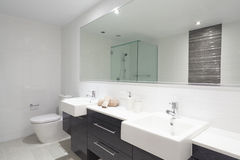 Modern twin bathroom. With sinks, toilet and shower Stock Photos