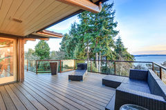 Modern two story panorama house with Puget Sound view. Modern two story panorama house boasts large deck furnished with wicker seats. Awesome sunset view of stock photo