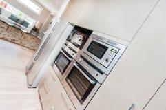 Modern ugn och kylskåp som fixas till väggen med skafferiskåp i köket arkivbilder