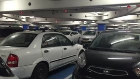 A modern underground car park. Shot containing of cars park at a modern underground car park stock footage