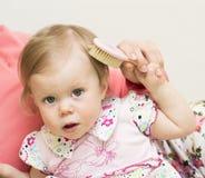 Modern undervisar dottern att borsta hår. Arkivfoto
