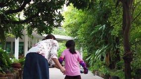 Modern undervisar hennes barn att rida en cykel arkivfilmer