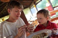 Modern undervisar hennes son att använda pinnar Arkivbild