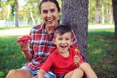 Modern ung mamma och hennes son som visar lycka under en gå royaltyfri fotografi