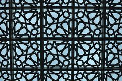 Traditional Islamic geometric pattern of a mosque. Modern and Unique Islamic Geometric pattern of a mosque glass ceiling with blue sky on the background Royalty Free Stock Images