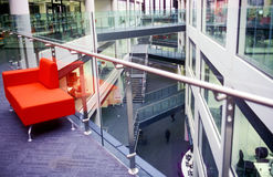 Modern university building. With multiple floors and a red sofa for relaxation stock photo