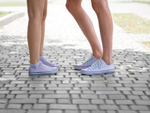 A close-up of teenages` legs in white sneakers talking to each other on a blurred cobbled background. Copy space. royalty free stock photography
