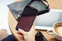 Modern urban lifestyle, Cafe hopper, Close up of women`s hands holding smart phone. Royalty Free Stock Images