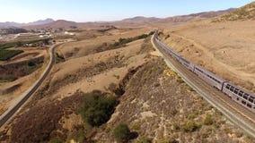 Modern urban passenger train moves through giant dry sand desert in steppe canyon hill landscape in 4k aerial drone shot. Modern urban passenger train moves stock video