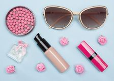 Modern urban woman essentials. Foundation, blusher, lipstick, perfume, sunglasses. Contents of cosmetic bag Royalty Free Stock Image